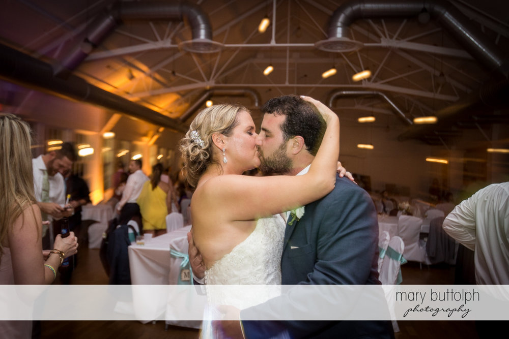 Couple kiss amid the din in the wedding venue at Emerson Park Pavilion Wedding