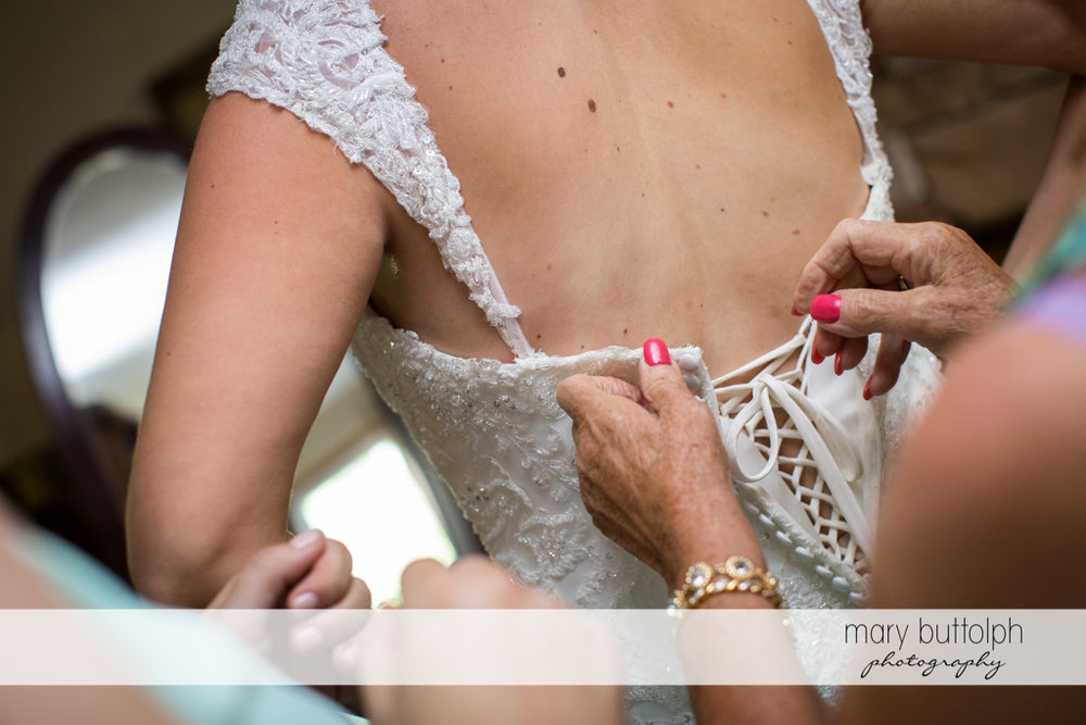 Friends help the bride slip into her wedding dress at Emerson Park Pavilion Wedding