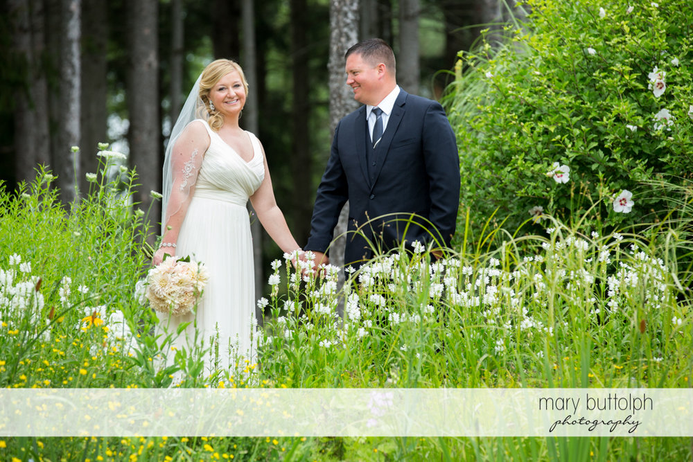 Couple hold hands in the woods at Emerson Park Pavilion Wedding