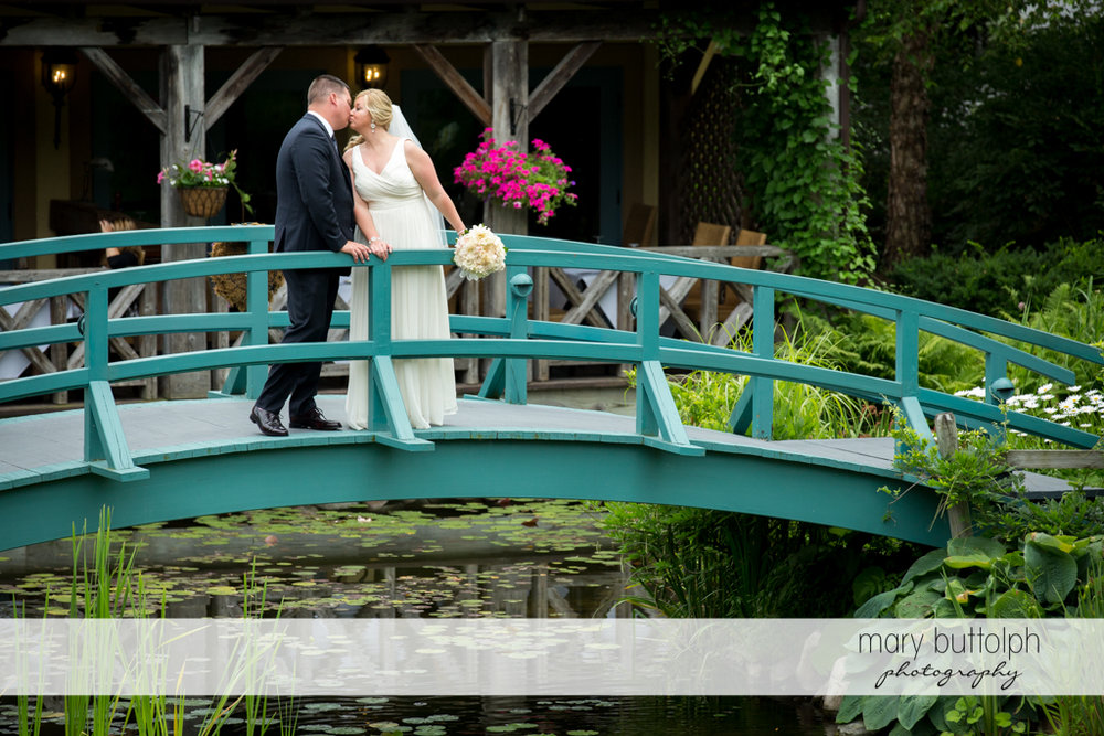 Couple kiss on the wooden bridge by the lake at Emerson Park Pavilion Wedding