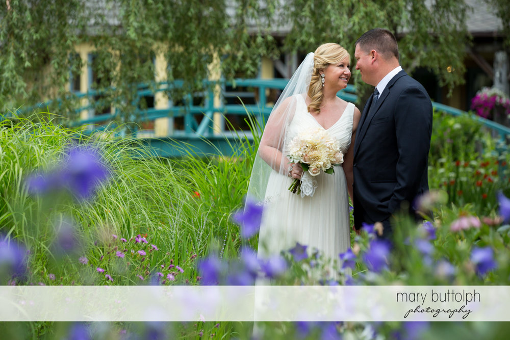 Couple share a romantic moment in the garden in front of the wooden bridge at Emerson Park Pavilion Wedding