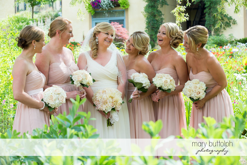 Bride and her bridesmaids with bouquets in the garden at Emerson Park Pavilion Wedding