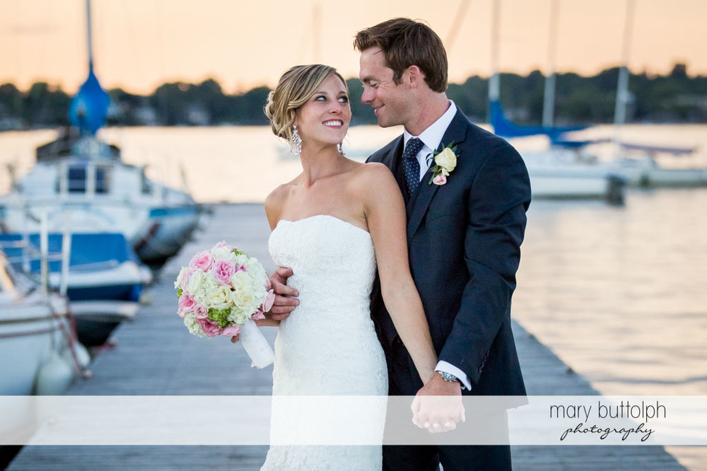 Couple hold hands on the docks at Skaneateles Country Club Wedding