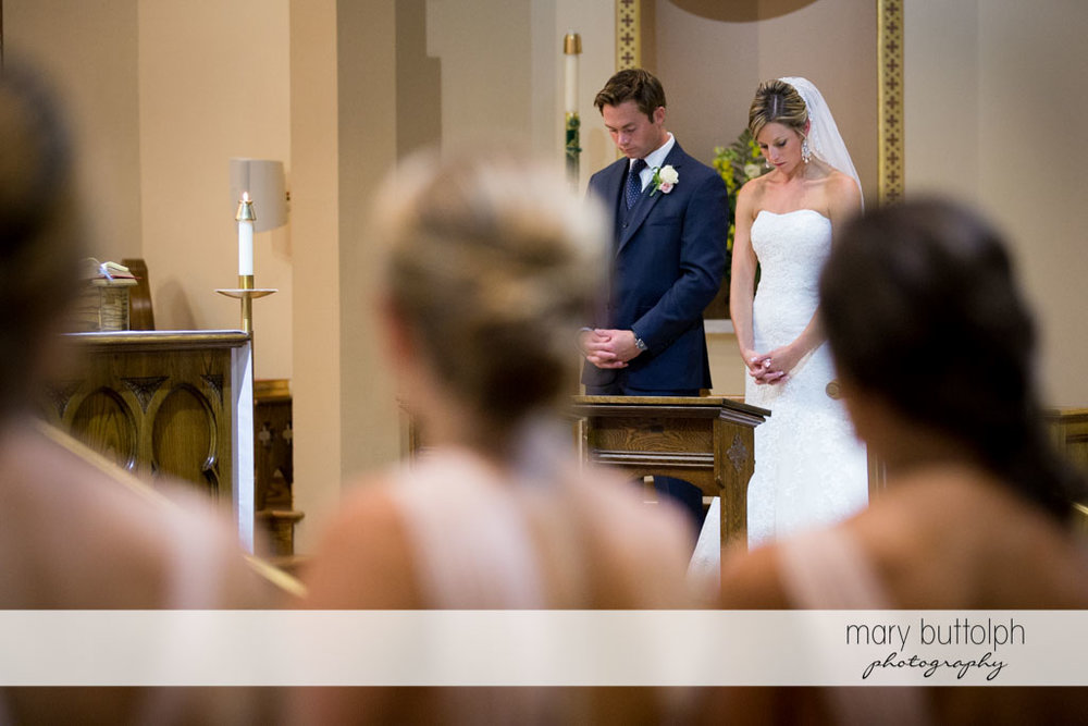 Couple praying in church as bridesmaids look on at Skaneateles Country Club Wedding