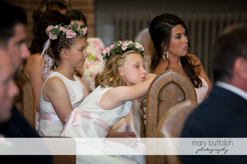 Girls with wreaths are among the guests in church at Skaneateles Country Club Wedding