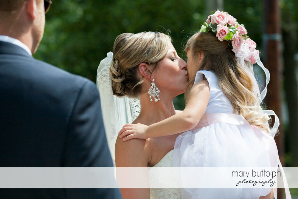 Bride kisses a young girl at Skaneateles Country Club Wedding