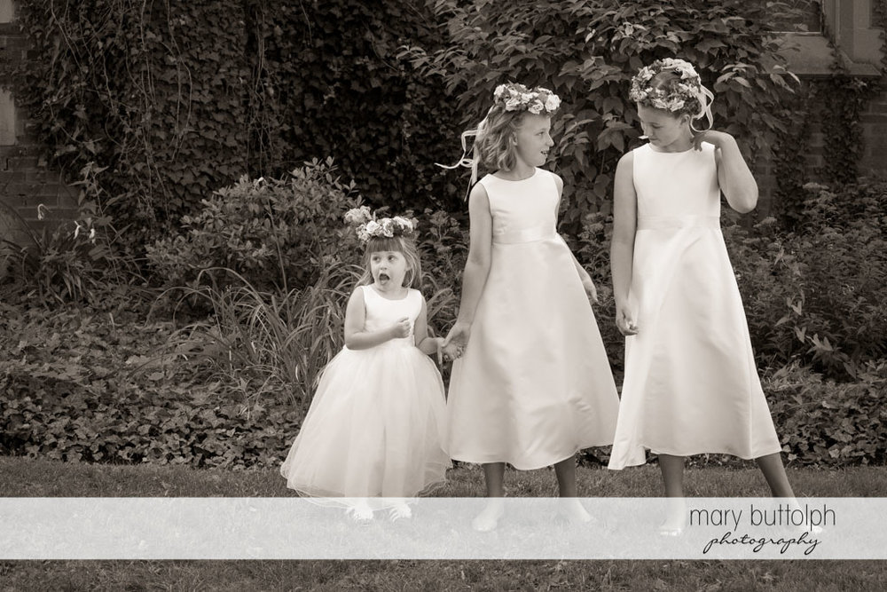 Three girls with wreaths wait in the garden at Skaneateles Country Club Wedding