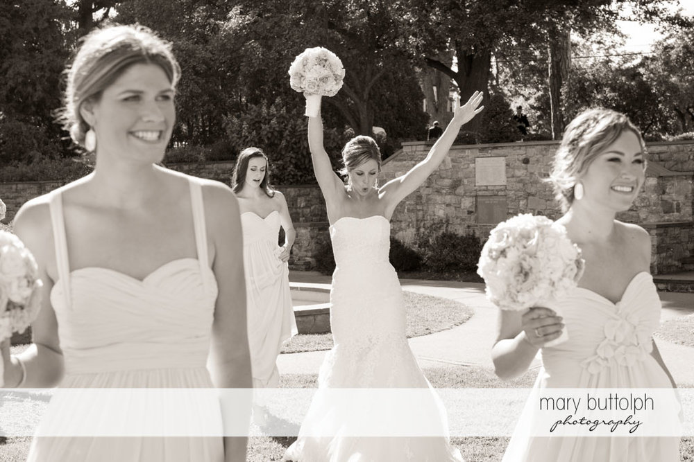 Bride and bridesmaids in a candid shot in the garden at Skaneateles Country Club Wedding