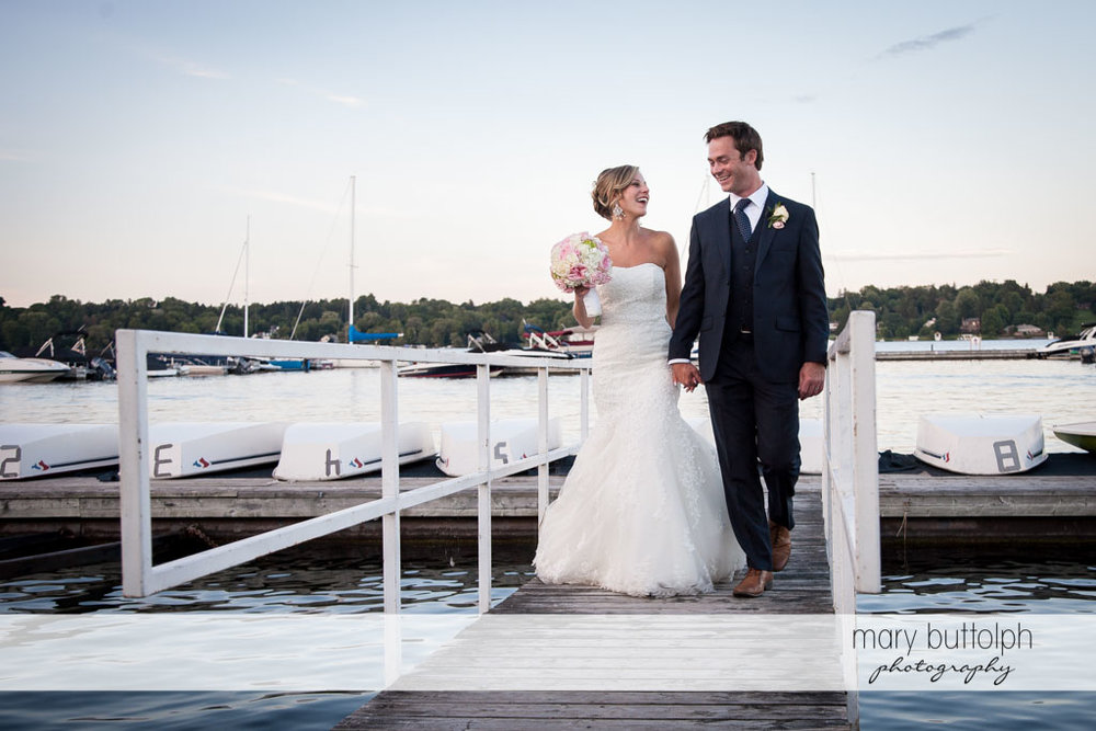Couple share a light moment on the docks at Skaneateles Country Club Wedding
