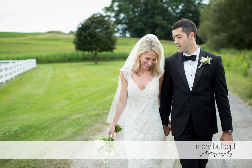 Couple stroll in the field at Skaneateles Country Club Wedding