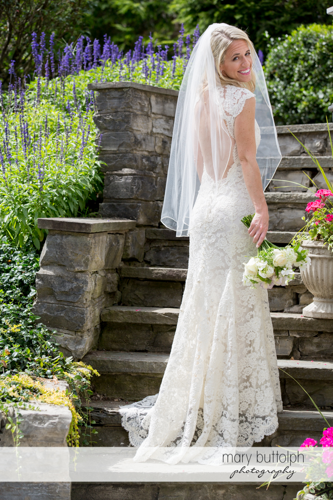 Bride poses at the stone steps at Skaneateles Country Club Wedding
