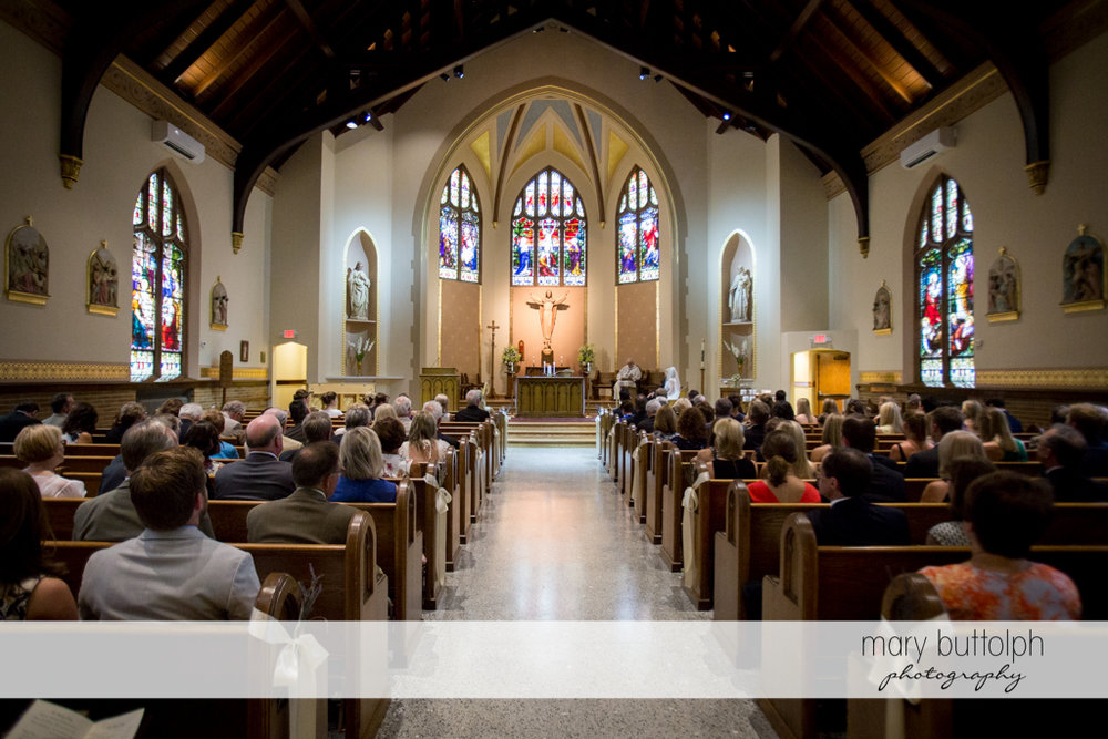 Long shot of the couple and priest in front of the altar at Skaneateles Country Club Wedding