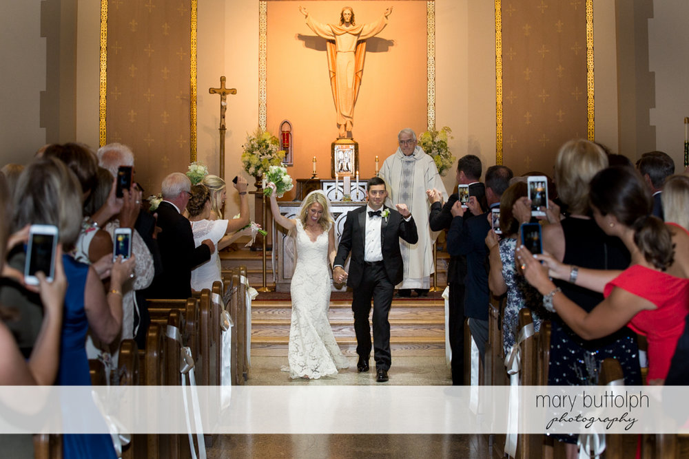 Guest take photos and videos of the couple leaving the church after the wedding at Skaneateles Country Club Wedding