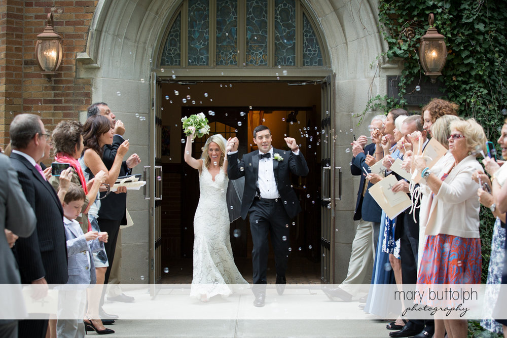 Couple are showered with bubbles as they leave the church at Skaneateles Country Club Wedding
