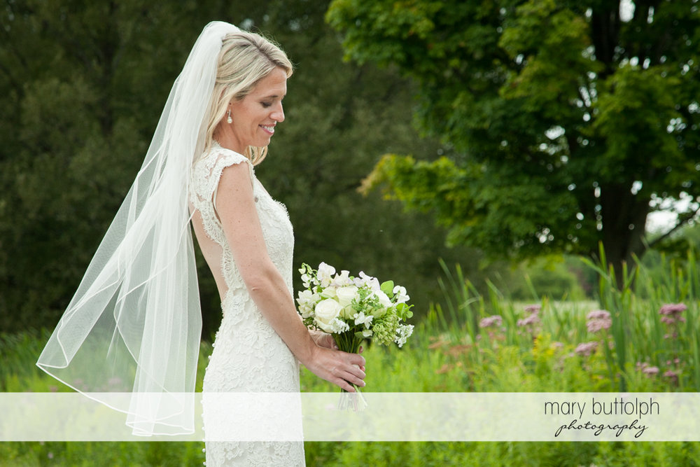 Bride holds a bouquet in the garden at Skaneateles Country Club Wedding
