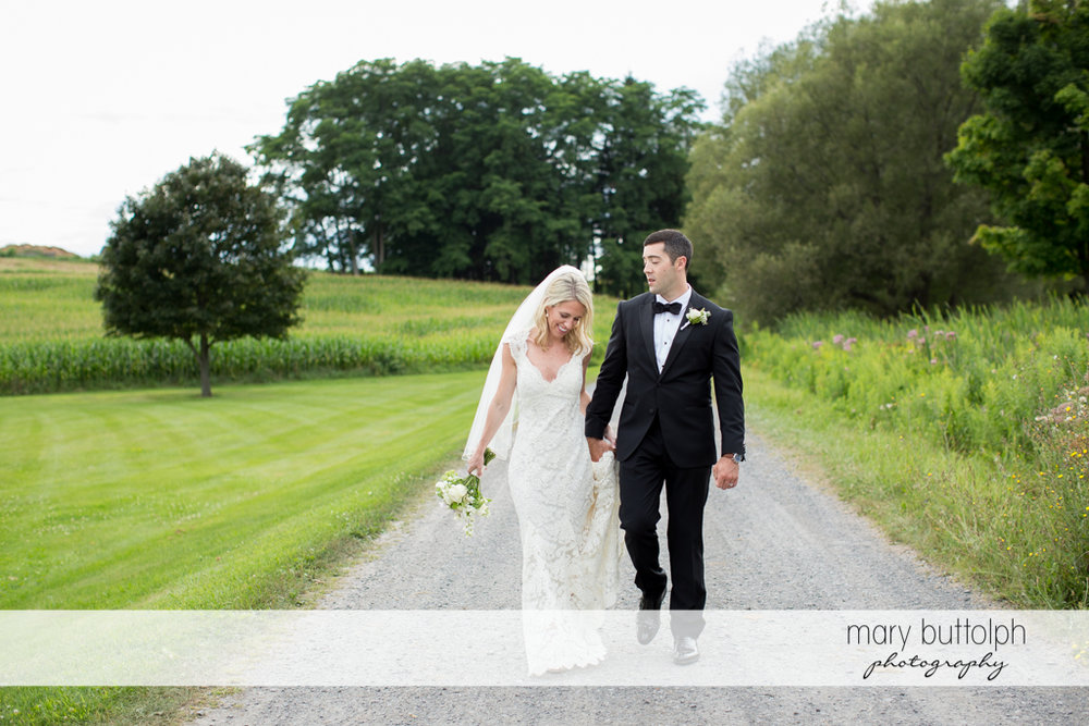 Couple walk up the road at Skaneateles Country Club Wedding