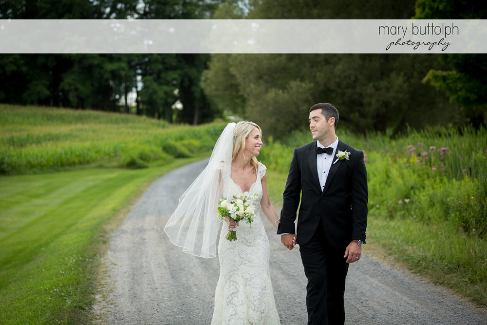 Couple take a stroll on the road at Skaneateles Country Club Wedding
