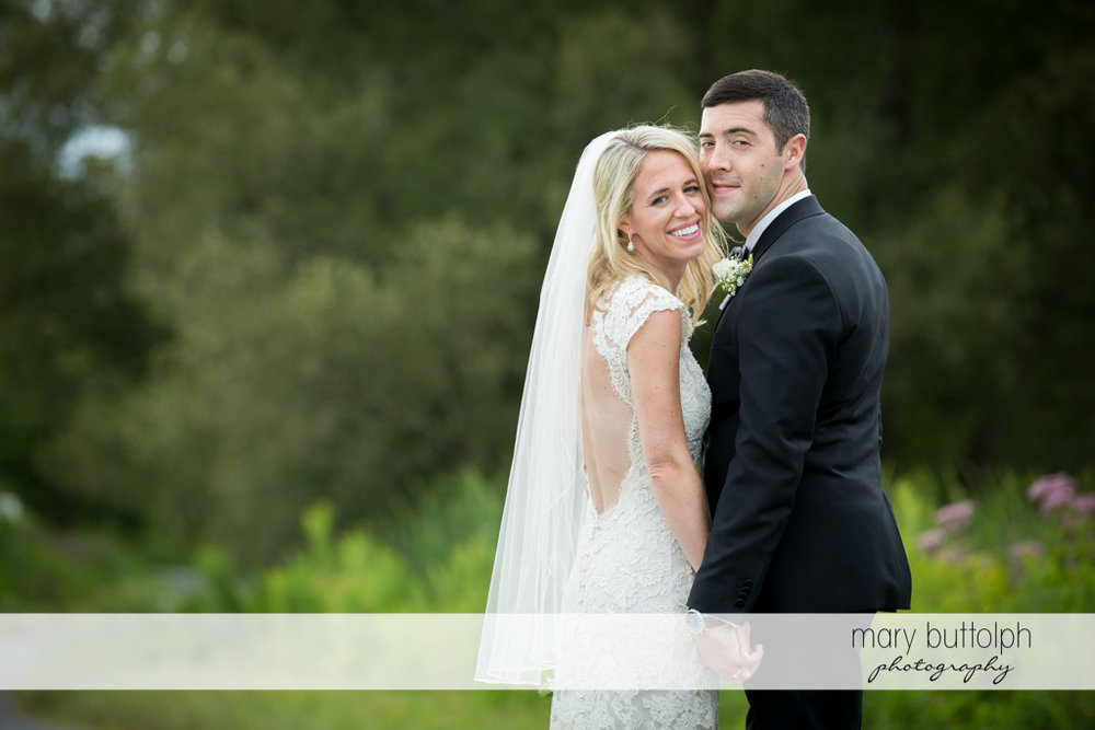 Couple smile for the camera in the garden at Skaneateles Country Club Wedding