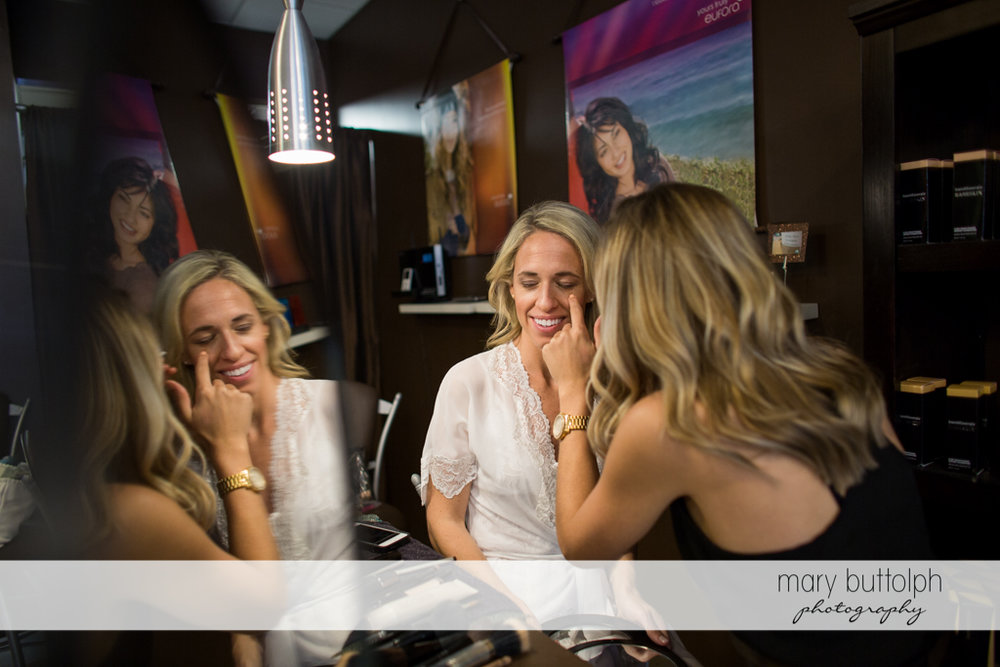Bride's reflection is seen in the mirror as she gets a makeover at Skaneateles Country Club Wedding