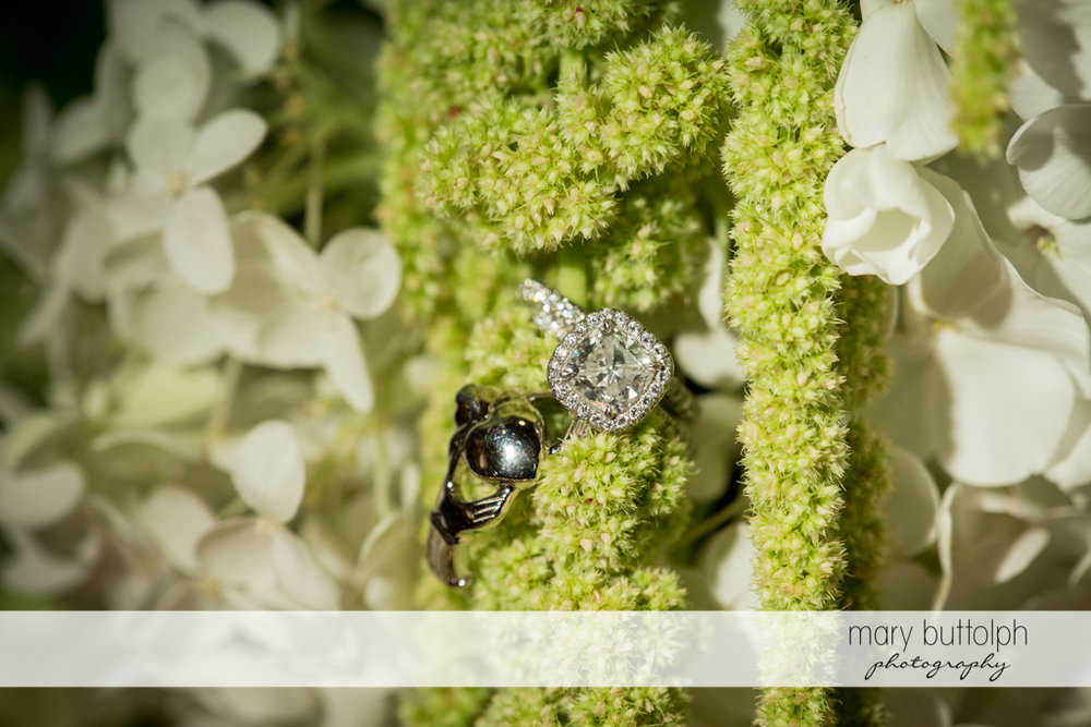 Couple's wedding rings with a bunch of flowers at Skaneateles Country Club Wedding