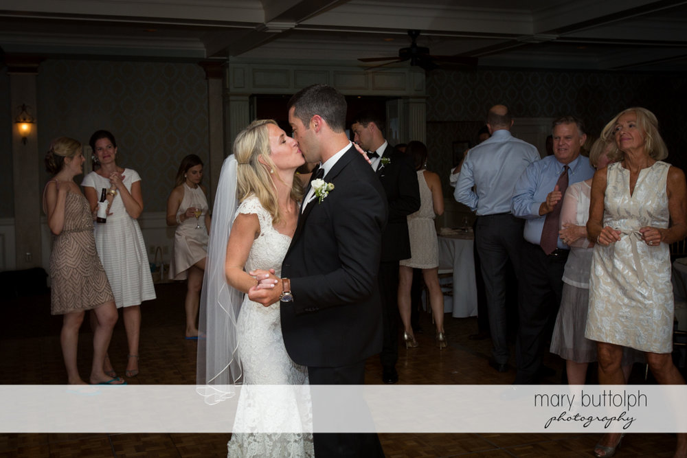 Couple kiss on the dance floor as guests look on at Skaneateles Country Club Wedding