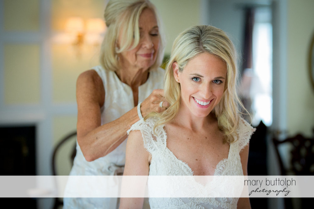 Bride's mother fixes her daughter's hair prior to the wedding at Skaneateles Country Club Wedding