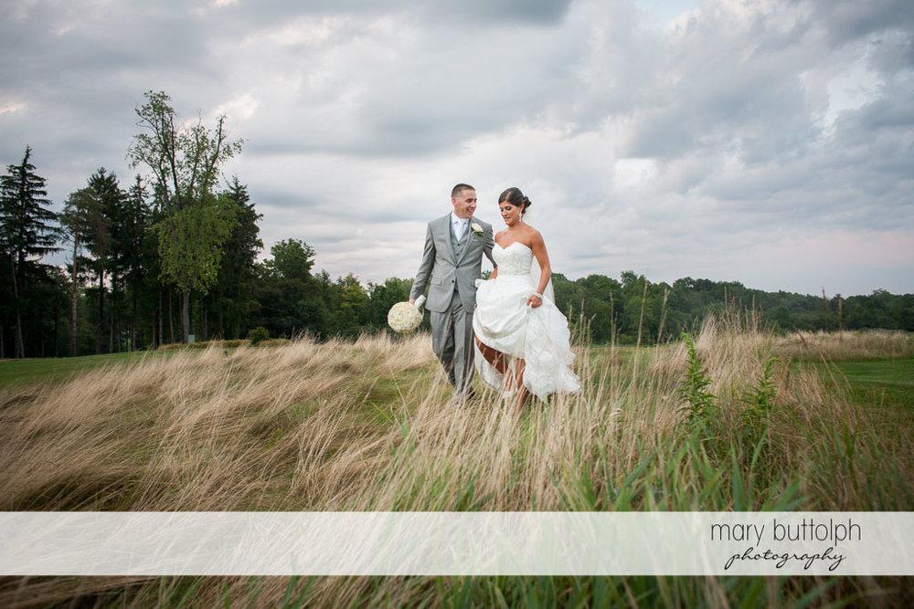 Couple cross the field at Turning Stone Resort Casino Wedding