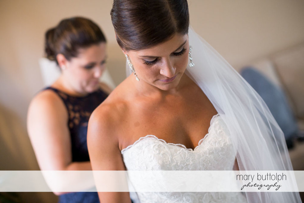 Bride waits patients as a friend fixes her wedding dress at Turning Stone Resort Casino Wedding