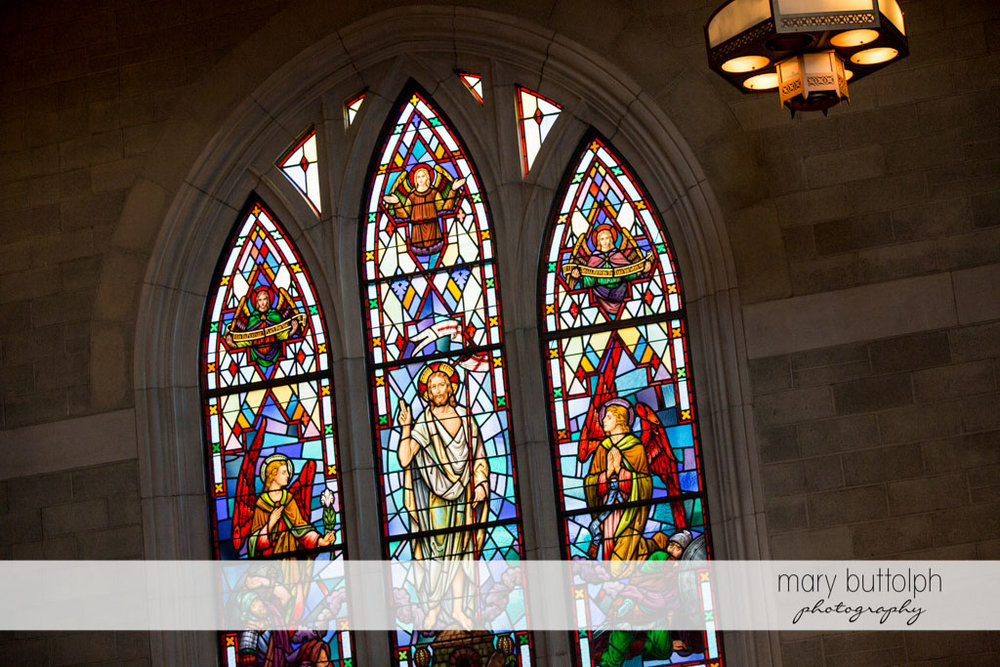 Church stained glass window shows Jesus and his angels at Turning Stone Resort Casino Wedding