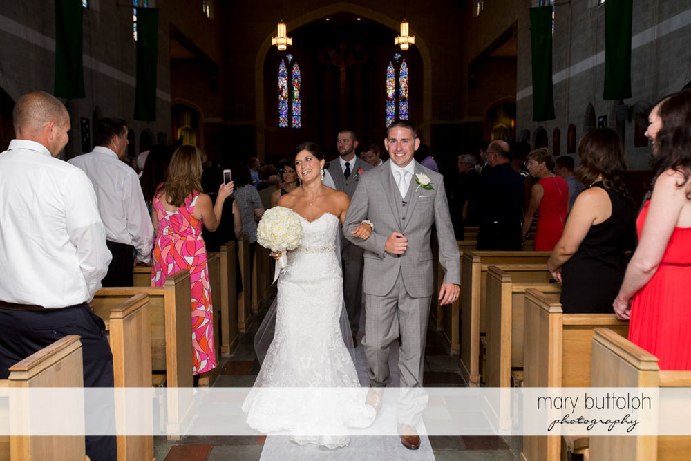 Couple leave church after the wedding as guests look on at Turning Stone Resort Casino Wedding