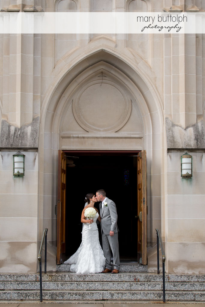Couple kiss in front of the church at Turning Stone Resort Casino Wedding