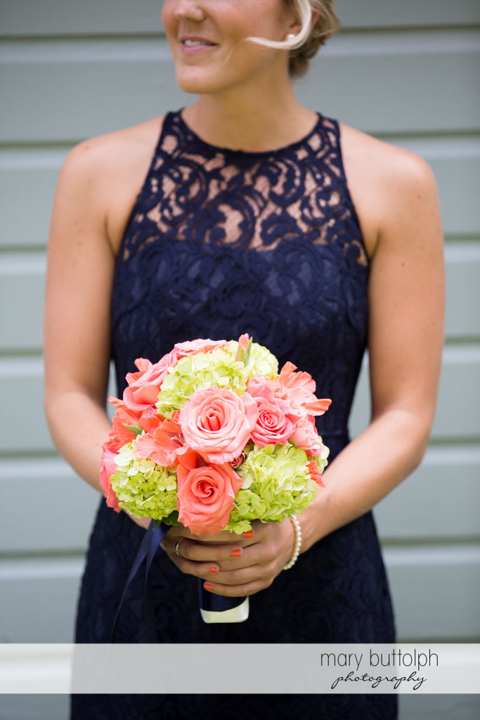 Bridesmaid in blue dress holding a bouquet at Turning Stone Resort Casino Wedding