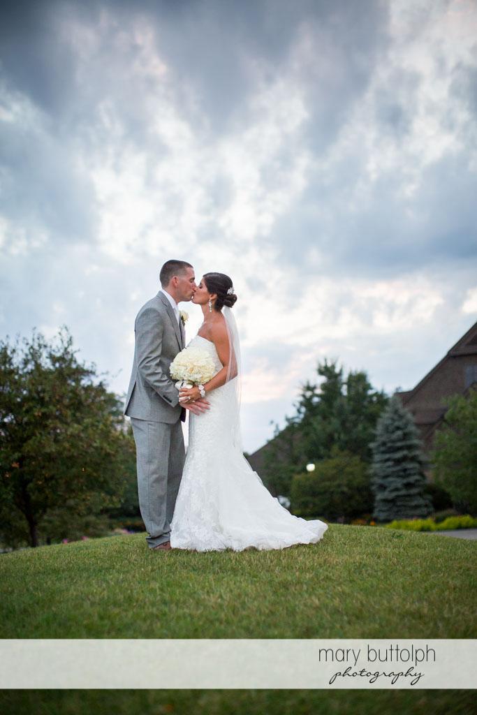 Couple kiss in the garden at Turning Stone Resort Casino Wedding