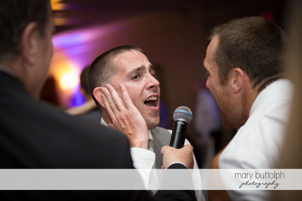 Groom sings with a guest at Turning Stone Resort Casino Wedding