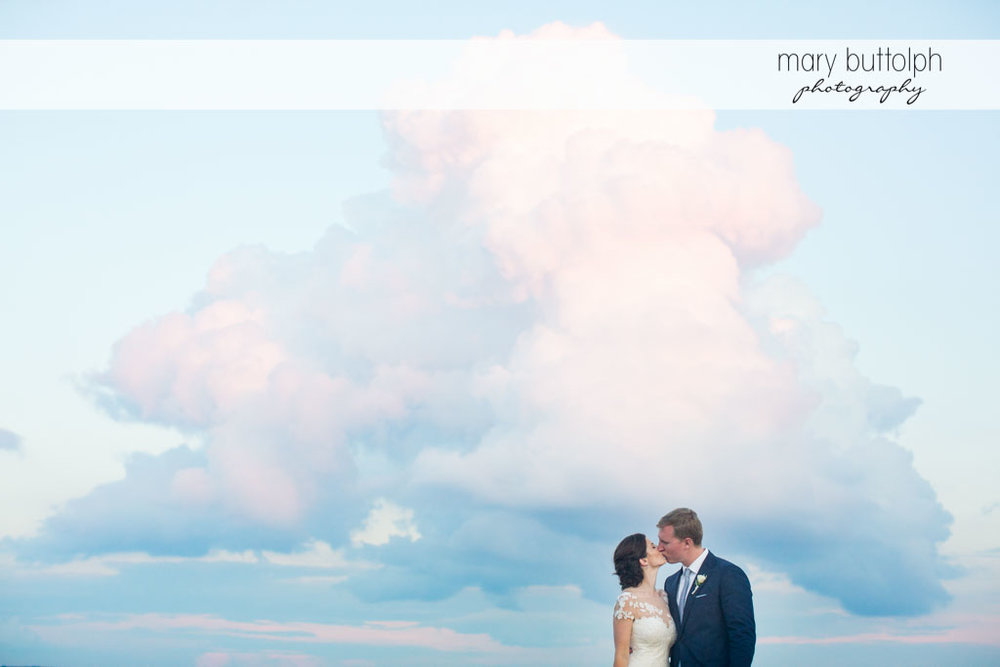 Couple kiss beneath the blue sky at Skaneateles Country Club Wedding