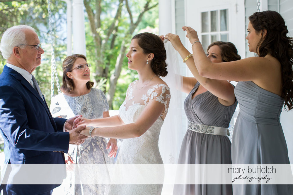 Bride and her father hold hands as the bridesmaids fix her hair pin at Skaneateles Country Club Wedding