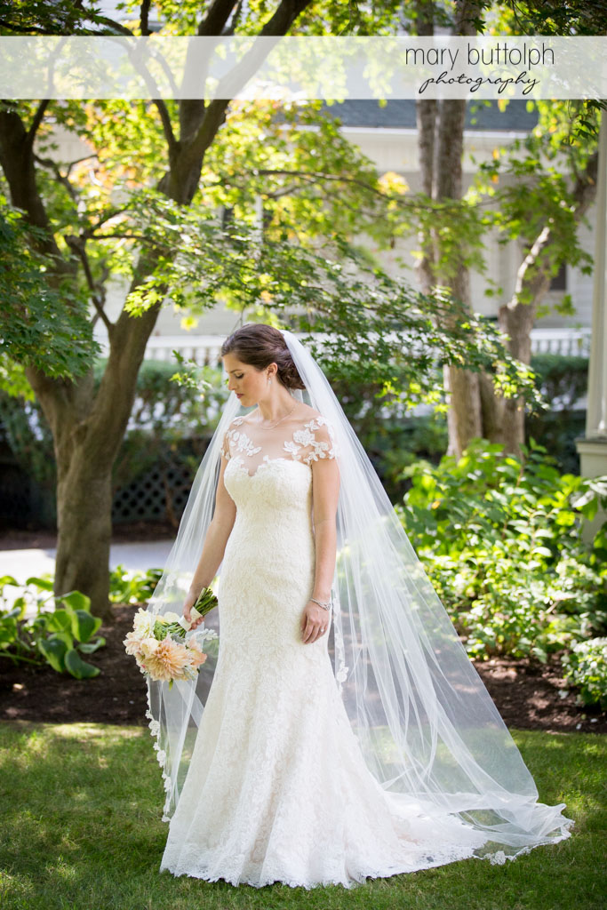 Bride with bouquet poses in the garden at Skaneateles Country Club Wedding