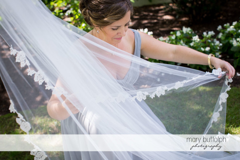 Bridesmaid fixes the bride's wedding veil in the garden at Skaneateles Country Club Wedding
