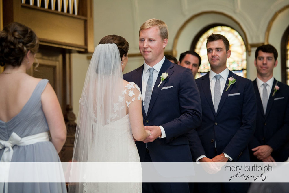Couple face each other as the groomsmen and bridesmaid look on at Skaneateles Country Club Wedding