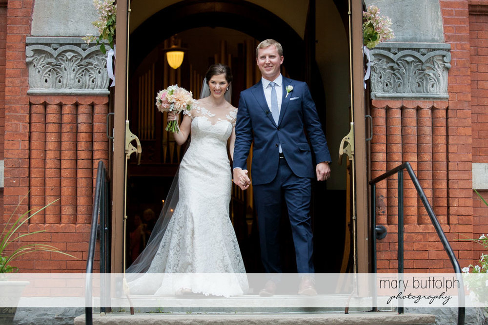 Couple leave church after the wedding at Skaneateles Country Club Wedding