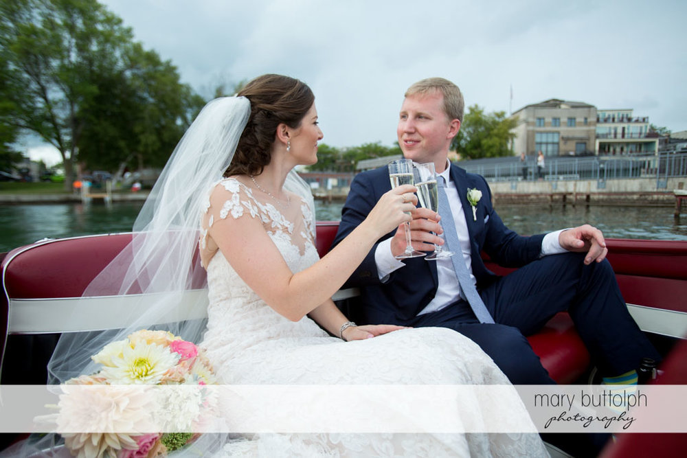 Couple make a toast in a boat at Skaneateles Country Club Wedding