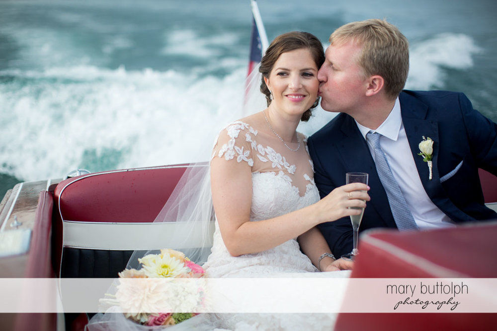 Groom kisses bride on the boat at Skaneateles Country Club Wedding