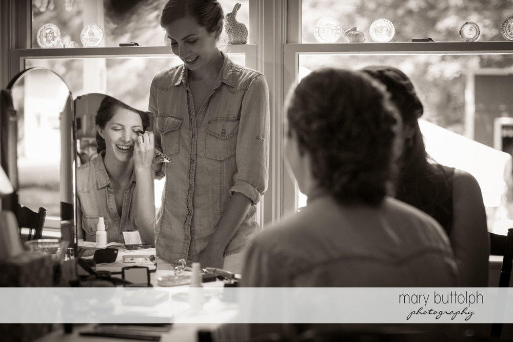 Bride puts on eye makeup as her friends look on at Skaneateles Country Club Wedding