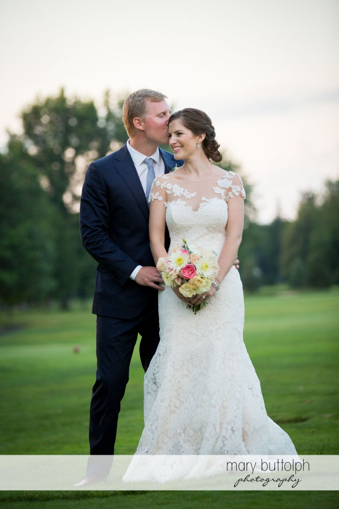 Groom kisses the bride in the garden at Skaneateles Country Club Wedding