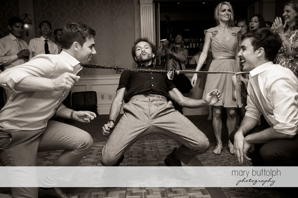 Guest dances the limbo using an improvised bar at Skaneateles Country Club Wedding
