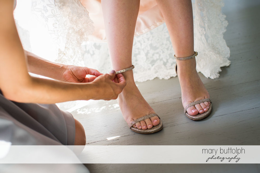 A friend puts an anklet on the bride's foot at Skaneateles Country Club Wedding