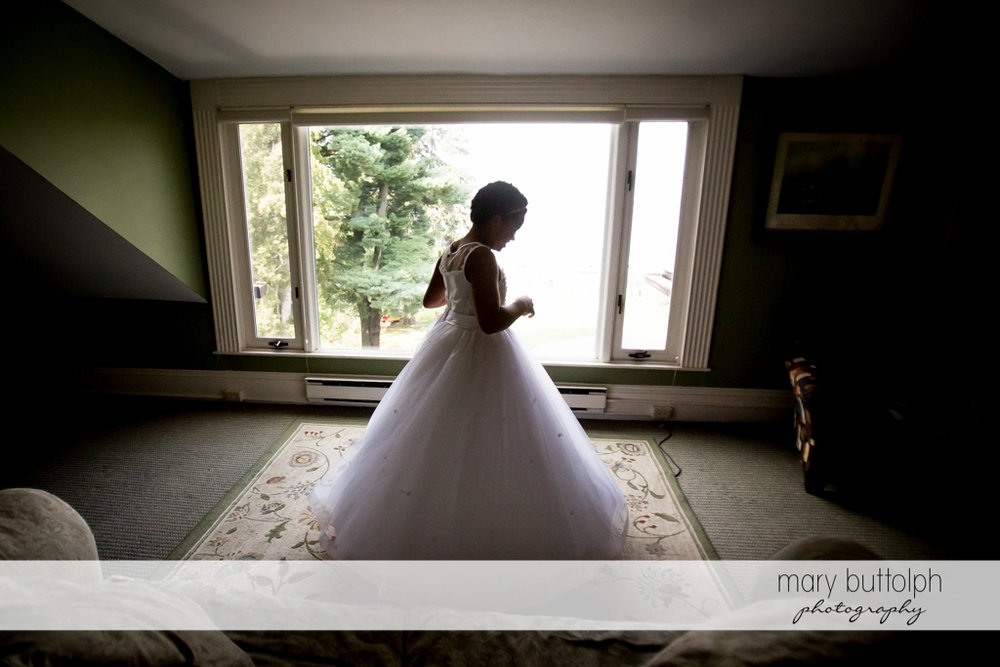 Flower girl stands in front of the window at the Brewster Inn Wedding
