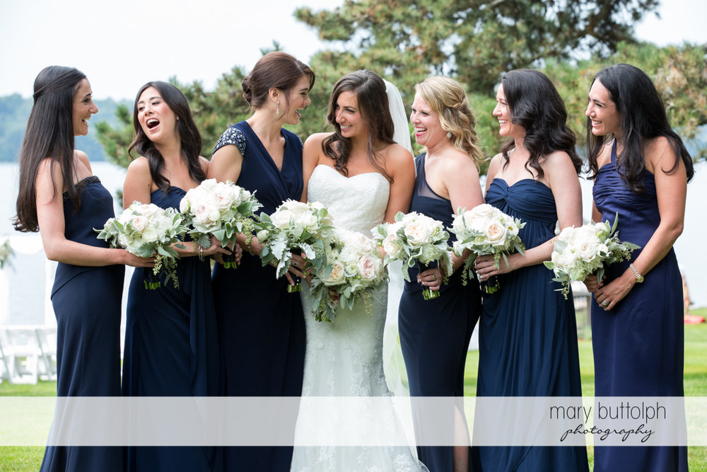 The bride and her bridesmaids holding bouquets in the garden at the Brewster Inn Wedding