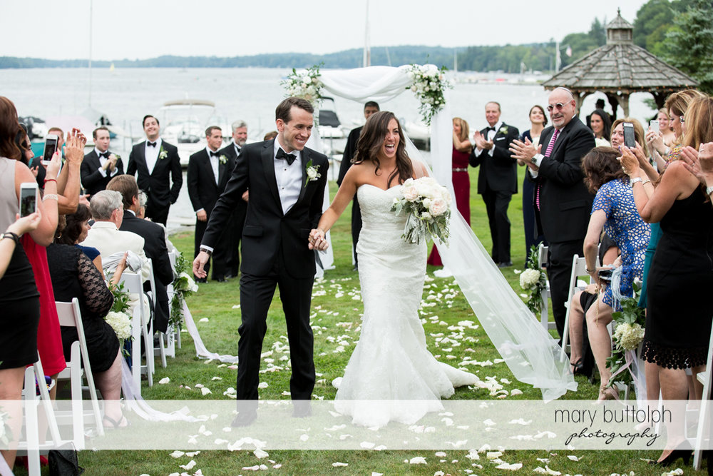 Couple leave after their garden wedding as they are applauded by guests at the Brewster Inn Wedding