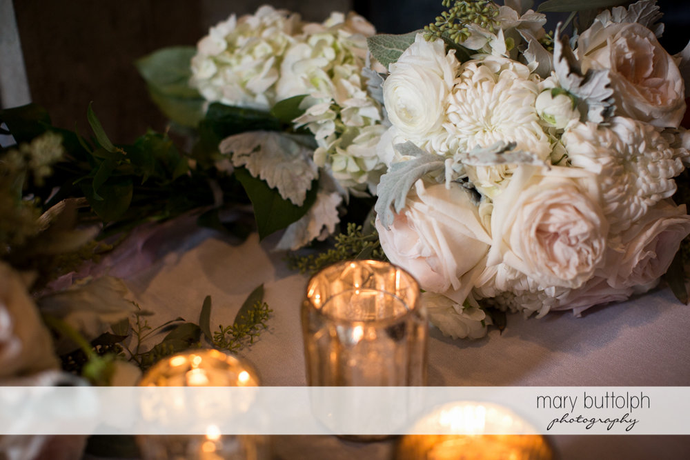 Close up shot of flowers and candles at the table at the Brewster Inn Wedding